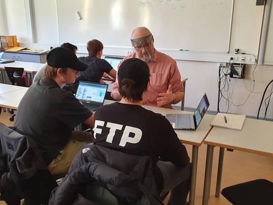 Her et  billede af underviseren der er i gang med at hjælpe en gruppe.
